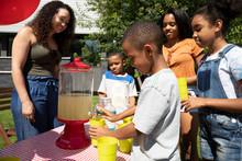 Boy Serving Lemonade At Lemonade Stand In Sunny, Summer Front Yard