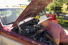 Mature Man Working On Pickup Truck With Hood Up