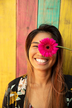Portrait Happy, Playful Young Woman Holding Vibrant Pink Gerber Daisy