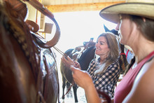 Mother And Daughter Saddling Horse Together In Stable