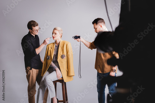 Fotografija selective focus of photographer shooting how Makeup Artist doing makeup to styli