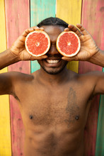 Portrait Playful Bare Chested Man Holding Grapefruit Slices Over Eyes On Summer Patio