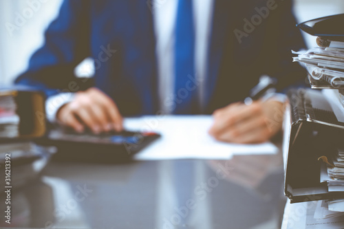 Fototapeta Binders with papers waiting to be processed with businessman or bookkeeper back in blur. Accounting planning budget. Audit, insurance and business concept obraz na płótnie