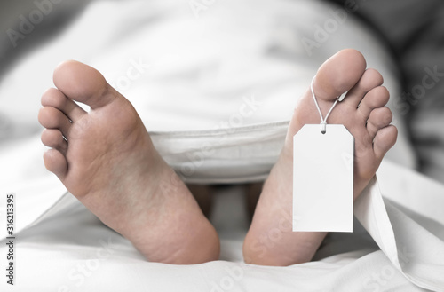 A dead man is lying in the morgue. Tag on the leg. Close up Canvas Print