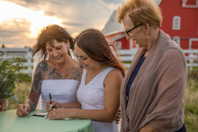 Wedding Officiant Watching Lesbian Brides Signing Marriage Certificate In Rural Field