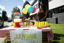 Mother And Twin Sons At Sunny, Summer Lemonade Stand In Front Yard Of House