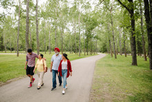 Indian Family Walking On Path In Park