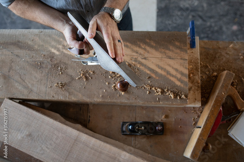 Overhead view of carpenter planing wood in workshop - 316215997