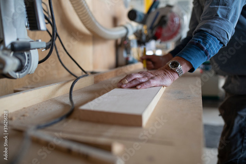Carpenter leaning on plank of wood in workshop - 316216128