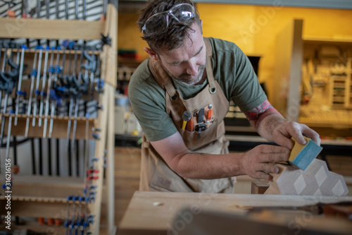 Man wearing apron sanding wood in workshop - 316216156