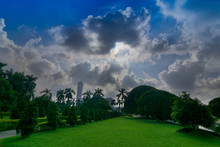 Sunrays Passing Through Tree Leaves And Falling On Green Grass In The Foreground, Morning At Kolkata, West Bengal, India