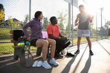 Three Tennis Players On Tennis Court Talking