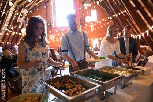 Bride and groom and wedding guests at wedding reception buffet line - 316217772