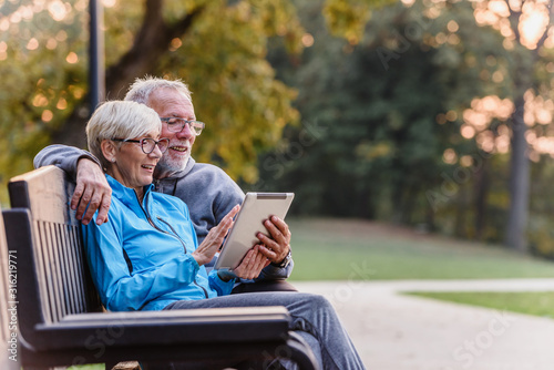 Smiling senior active couple sitting on the bench looking at tablet computer. Using modern technology by elderly.