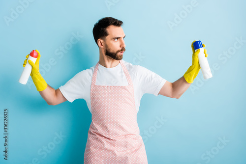 serious bearded man holding spray bottles on blue