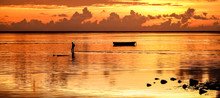 Sunset At Mauritius Island With Silhouette Of Unrecognizable Fisherman Going Home After A Day Of Fishing - Wanderlust And Travel Concept On Orange Sunlight Filter