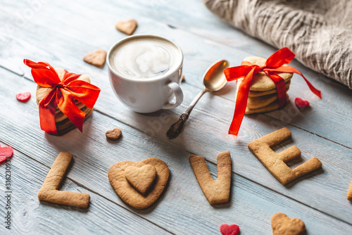 Cup of coffee and a message from a sweet cookie in the form of the word love. Romantic Valentine's day gift