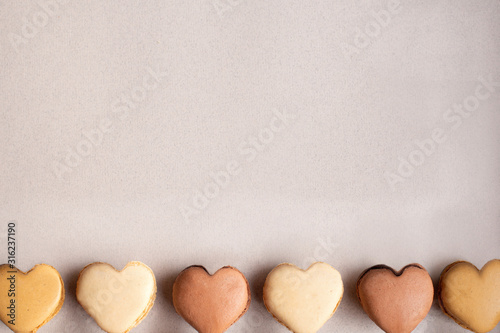 Colorful heart-shaped macaroons in a row on pastel background Wallpaper Mural