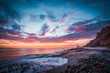 canvas print picture - Beautiful beach sunset with a rocky shore