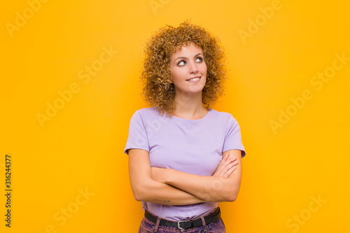 young afro woman feeling happy, proud and hopeful, wondering or thinking, lookin Canvas Print
