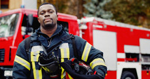 Portrait Of African American Firefighter In Protective Suit With Oxygen Mask And Helmet In Hands. Firefighter Portrait On Duty..