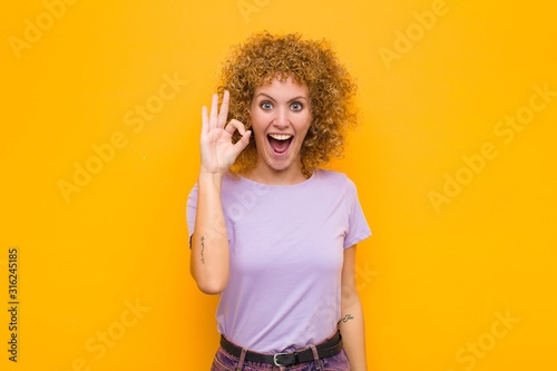 Fotografie, Obraz  young afro woman feeling successful and satisfied, smiling with mouth wide open,
