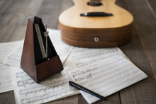 Still Life Of Metronome, Sheet Music And Guitar