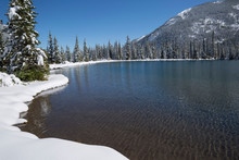 Sunny Blue Pond Surrounded By Snow Below Mountain, Forget Me Not Pond, Alberta, Canada