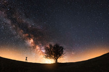 Night Landscape. The Camera On The Tripod And Tree Silhouette On The Hill Under The Bright Beautiful Milky Way Galaxy.