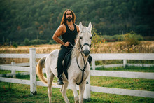 Equestrian And Animal Love Concept. Rider On Gray Arabian Horse In The Field. Handsome Bearded Man Riding Horse At Farm. Beautiful Horse With Man Rider Trotting On Autumnal Field.