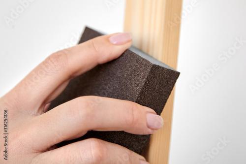 Grinding sponge block in female hand Fototapeta