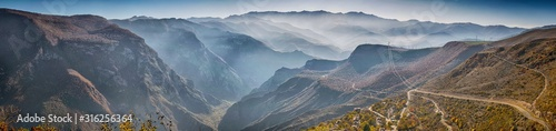 Obraz Beautiful panoramic view from the top of tatev gorge while the famous longest cable car Wings of Tatev and small village. South Armenian autumn landscape with Caucasus mountain range and foggy canyon - fototapety do salonu