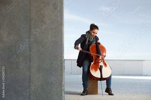 Fotografía beautiful girl plays the cello with passion in a concrete environment