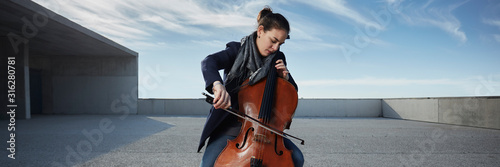 Obraz beautiful girl plays the cello with passion in a concrete environment - fototapety do salonu