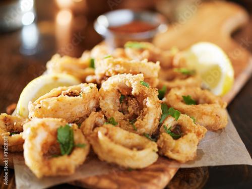 Fototapeta crispy fried calamari rings wih marinara dipping sauce and lemon obraz