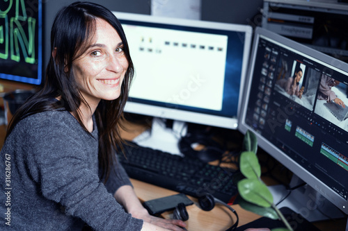 Obraz A Young Dark-haired Female Video Maker Smiles While Working At Computer In A Photo Studio - fototapety do salonu