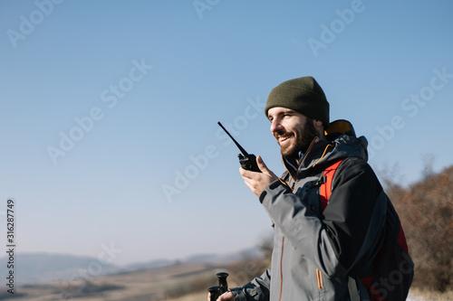 Fotografija Smiling man speaking on two-way radio for hiking
