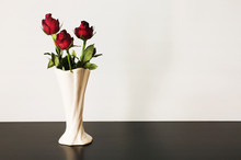 Three Red Roses In Vase On Whi...