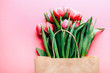 Beautiful tulips bouquet in bag on pink background