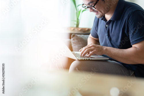 Obraz using computer.asian man hand typing message keyboard laptop shopping online.search information form internet while sitting on sofa.concept use technology device contact communication business - fototapety do salonu