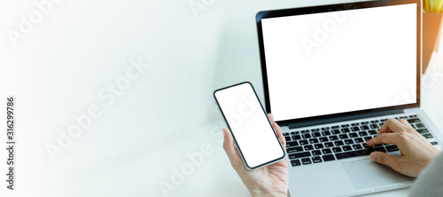 Photo mockup image blank screen computer,cell phone with white background for advertising text,hand man using laptop texting mobile contact business search information on desk in cafe