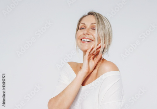 Beauty portrait of blonde smiling laughing woman 35 year plus clean fresh face with close eyes isolated on white background