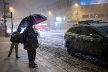 Man Is Standing Outside With Umbrella In The Extreme Cold And Snow In Chicago Area During A Blizzard During A Winter Night In January.  Traffic Is Slowing Down Due To Weather Conditions