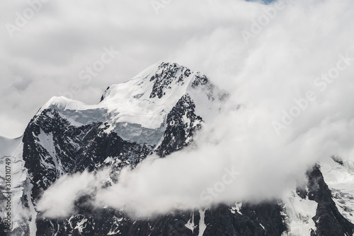 Fototapeta Atmospheric minimalist alpine landscape with massive hanging glacier on snowy mountain peak