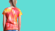 View From The Back Of A Girl In A T-shirt In The Style Of Tie Dye On A Turquoise Background.