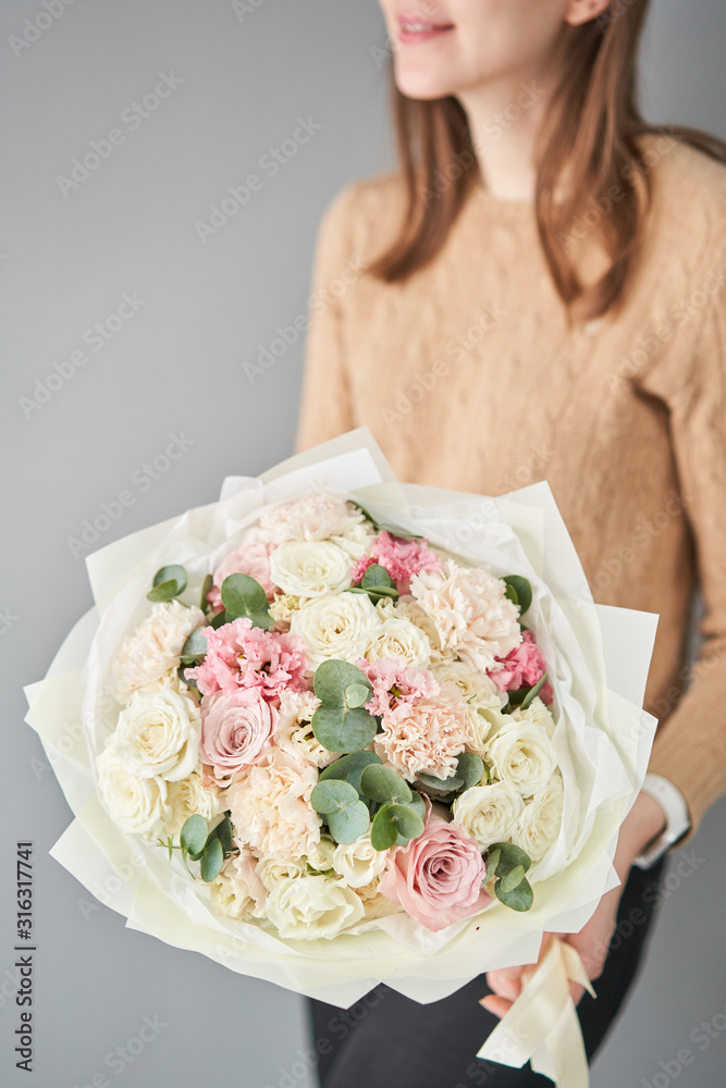 Obraz European floral shop. Beautiful bouquet of mixed flowers in womans hands. the work of the florist at a flower shop. Delivery fresh cut flower. fototapeta, plakat