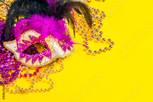 Canvas Print Festive Carnival mask and beads on yellow background.