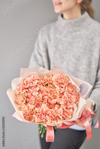 Obraz Bouquet of carnation flowers pastel color. Spring bunch in woman hand. Present for Mothers Day. - fototapety do salonu
