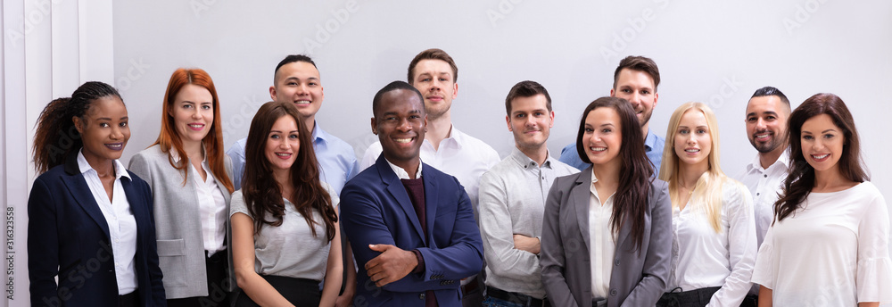 Fototapeta Group Of Smiling Businesspeople Standing In Office