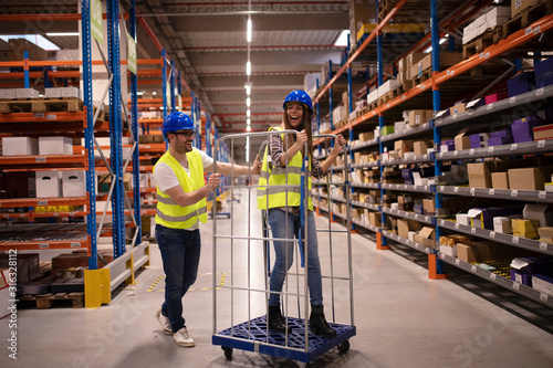 Fototapeta Workers having fun at work in warehouse storage area. Happy warehouse workers playing with cart and pushing each other. Break time. obraz